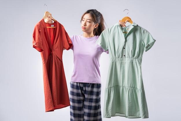 Młoda azjatka zastanawia się nad wyborem sukienki do noszenia