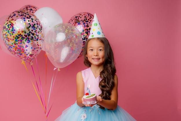 Młoda azjatka zdmuchuje różową świeczkę na przyjęciu urodzinowym