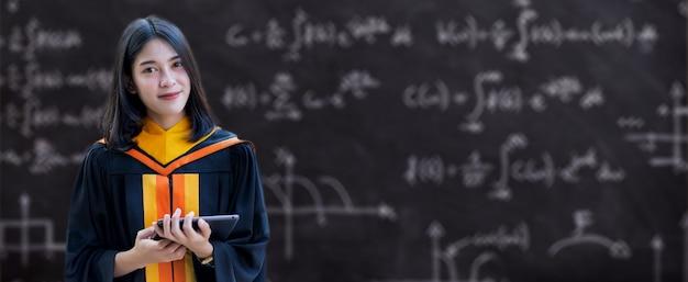 Młoda azjatycka absolwentka uniwersytetu w sukni ukończenia szkoły i tablicy zaprawowej posiada dyplom ukończenia studiów