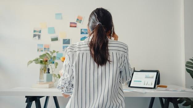 Młoda azjatycka biznesowa dama rozmawia przez telefon z kolegami o pracy