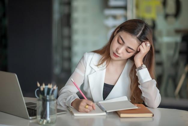 Młoda azjatycka biznesowa kobieta czuje się chora i zmęczona lub wyczerpana pracą biurową.