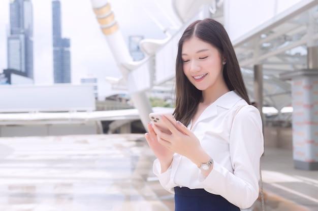 Młoda azjatycka biznesowa kobieta, która uśmiecha się, bawi się i patrzy na smartfona w swoich rękach