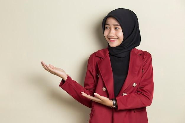 Młoda azjatycka biznesowa kobieta nosi hidżab uśmiechnięta pewnie wskazując palcami w różnych kierunkach.