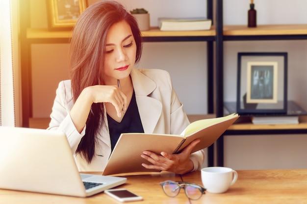 Młoda azjatycka biznesowa kobieta pracuje przy miejscem pracy.