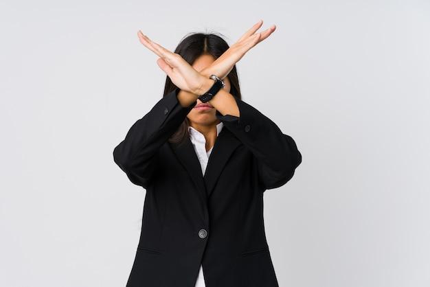 Młoda azjatycka biznesowa kobieta trzymając dwie skrzyżowane ręce
