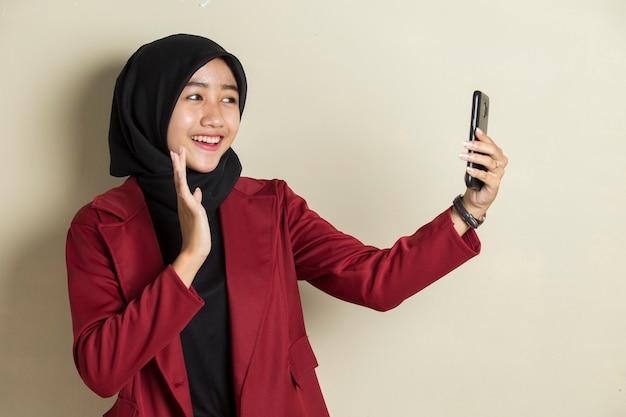 Młoda azjatycka biznesowa kobieta ubrana w hidżab, nawiązywanie połączenia wideo za pomocą inteligentnego telefonu