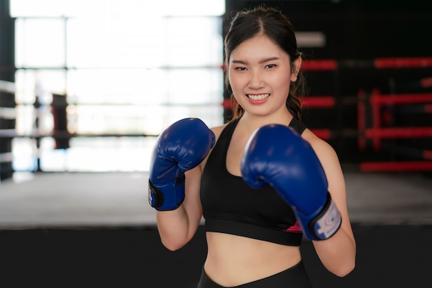Młoda azjatycka bokserska sprawności fizycznej kobieta ono uśmiecha się szczęśliwy jest ubranym błękitne bokserskie rękawiczki