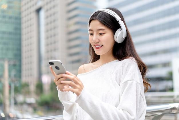 Młoda azjatycka dziewczyna jest ubranym hełmofony słucha muzyka od telefonu komórkowego przeciw miasto budynkowi