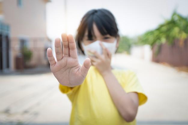 Młoda azjatycka dziewczyna jest ubranym maskę dla ochrony covid 19, tajlandzki dzieciak jest ubranym maskę przeciwpyłową. dla ochrony pm2.5 i pokazania gestu zatrzymania rąk dla wybuchu epidemii wirusa korony.