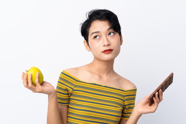 Młoda azjatycka dziewczyna ma wątpliwości podczas gdy biorąc czekoladową tabletkę w jednej ręce i jabłko w drugiej