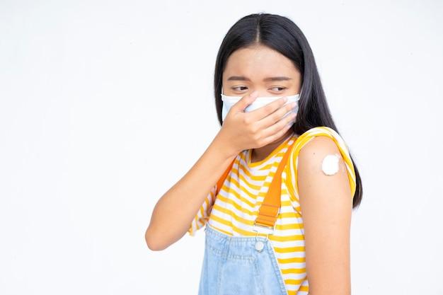 Młoda azjatycka dziewczyna pokazująca ramię po szczepieniu na białym tle