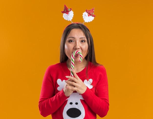 Młoda azjatycka dziewczyna ubrana w boże narodzenie obręcz do włosów ze swetrem trzymając świąteczne cukierki na białym tle na pomarańczowej ścianie