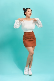 Młoda azjatycka dziewczyna wskazuje w dół ubranie ubranie
