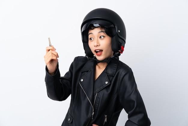 Młoda azjatycka dziewczyna z hełma motocyklem i kluczem nad odosobnioną biel ścianą