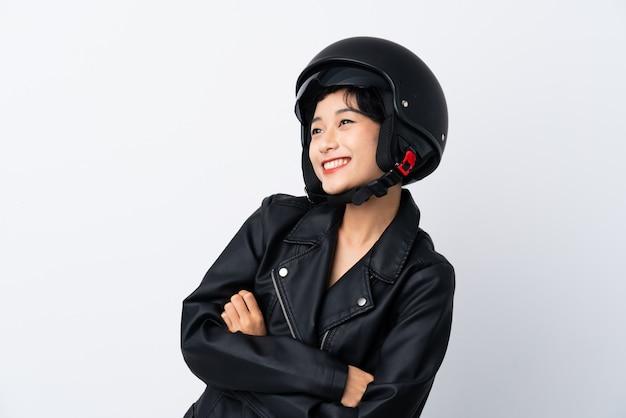 Młoda azjatycka dziewczyna z motocyklu hełmem nad odosobnioną biel ścianą