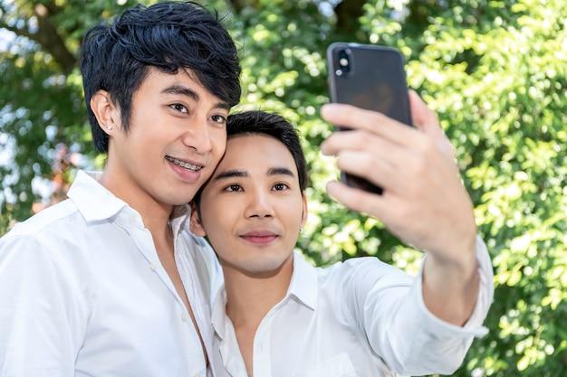 Młoda azjatycka homoseksualna para bierze autoportret z mądrze telefonem
