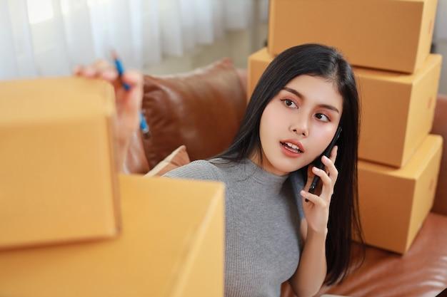 Młoda azjatycka, inteligentna i aktywna kobieta w swobodnej sukience, sprawdzająca i pracująca w domu ze smartfonem i opakowaniem w pudełku na zakupy online (nowa normalna koncepcja)