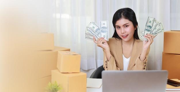 Młoda azjatycka inteligentna i szczęśliwa kobieta w swobodnej sukience pokazująca banknot z ekscytującymi emocjami i pracująca na komputerze w celu zamówienia zakupów online i pakowania pudełek na stole (nowa normalna koncepcja)