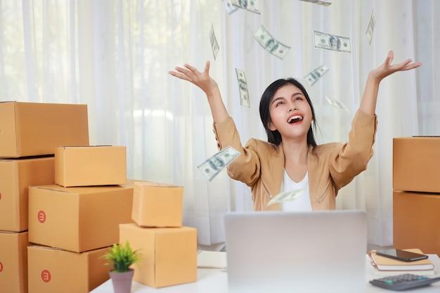 Młoda azjatycka inteligentna i szczęśliwa kobieta w swobodnej sukience pracująca w domu z laptopem i zamówieniem zakupów online i opakowaniem pudełkowym na stole ze spadającymi banknotami (nowa normalna koncepcja)
