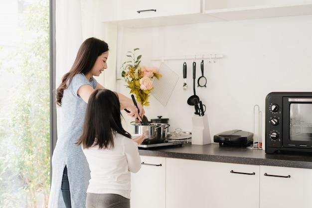 Młoda azjatycka japońska mama i córka gotuje w domu. styl życia kobiety szczęśliwe robi makaronowi i spaghetti wpólnie dla śniadaniowego posiłku w nowożytnej kuchni przy domem w ranku.