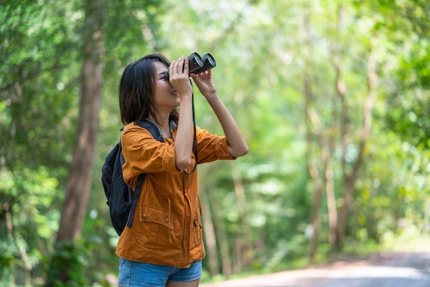 Młoda azjatycka kobieta backpacker z teleskopem lornetki patrząc na ptaki w lesie na wakacjach w lecie