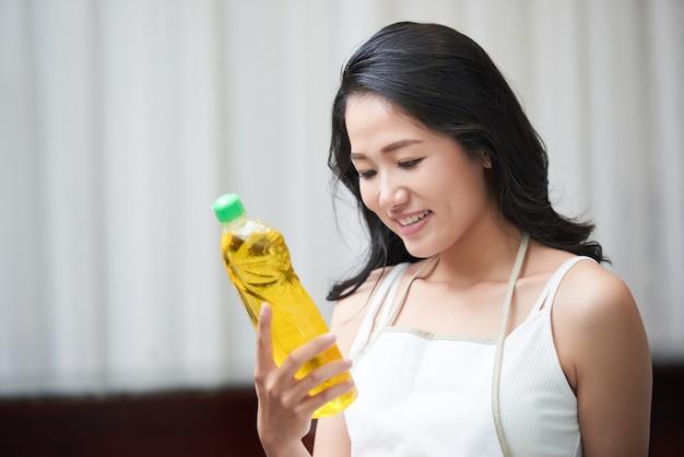 Młoda azjatycka kobieta bada detergentową butelkę