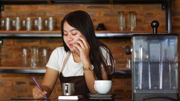 Młoda azjatycka kobieta barista nosi fartuch rozmawiając i odbiera zamówienie od klienta na telefon komórkowy w kawiarni. koncepcja sklepu kawiarnianego małej firmy. kobieta barman pisanie notatki podczas słuchania klienta