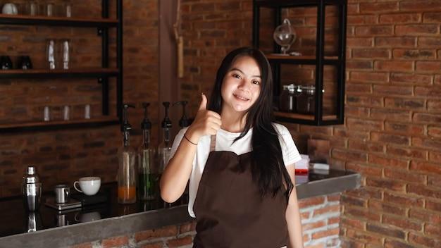 Młoda azjatycka kobieta barista nosić fartuch ok gest
