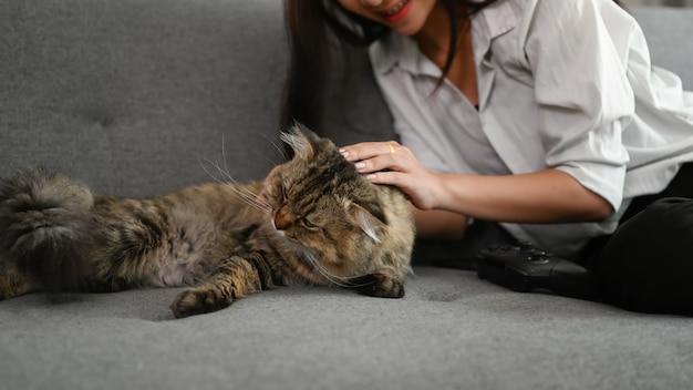 Młoda azjatycka kobieta bawi się swoim kotem