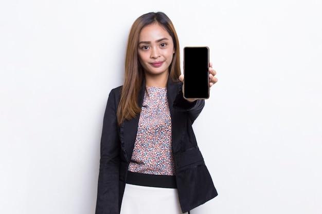 Młoda azjatycka kobieta biznesu demonstruje telefon komórkowy na białym tle