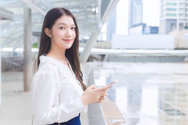 Młoda azjatycka kobieta biznesu idzie do biura lub miejsca pracy, które patrzy na aparat trzyma smartfon w dłoniach w wielkim mieście z budynkami biznesowymi z miastem w tle.
