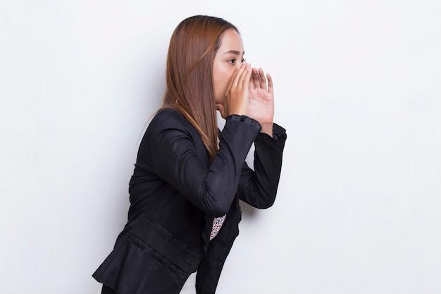 Młoda azjatycka kobieta biznesu krzyczy i krzyczy ogłaszając na białym tle