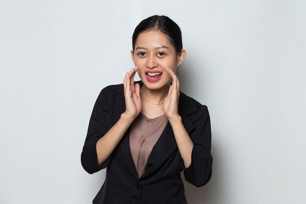 Młoda azjatycka kobieta biznesu krzyczy, krzyczy i ogłasza