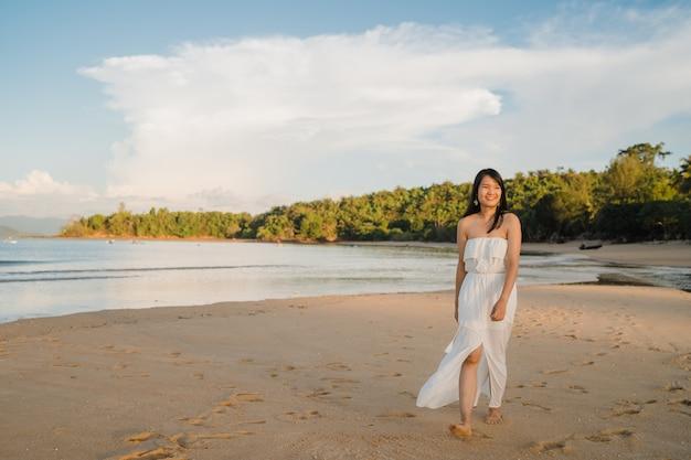 Młoda azjatycka kobieta chodzi na plaży. piękny żeński szczęśliwy relaksuje chodzić na plaży blisko morza gdy zmierzch w wieczór.