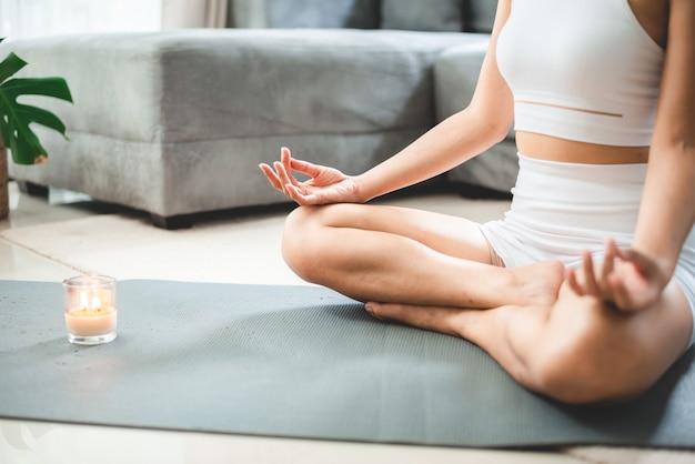 Młoda azjatycka kobieta ćwiczenia jogi w domu siłownia, zdrowy styl życia kobiet z treningiem sportowym fitness w domu, dziewczyna robi ciało aktywne ćwiczenia fizyczne kryty dom pokój, relaks i odnowa biologiczna