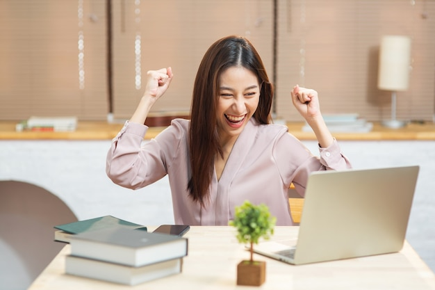 Młoda azjatycka kobieta czuje się podekscytowany, patrząc na laptopa na rozpoczęcie małej firmy w domu