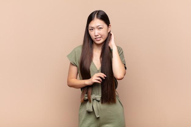 Młoda azjatycka kobieta czuje się zestresowana, sfrustrowana i zmęczona, ociera bolącą szyję, ze zmartwionym, zmartwionym spojrzeniem
