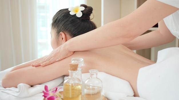 Młoda azjatycka kobieta dostaje relaksującego olejowego masaż przy piękno zdroju salonem. masaż dla zdrowia
