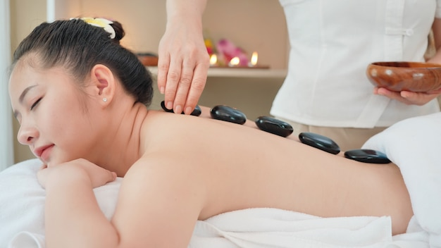 Młoda azjatycka kobieta dostaje zdroju masaż z gorącym kamiennym masażem w piękno zdroju salonie. masaż relaksacyjny dla zdrowia