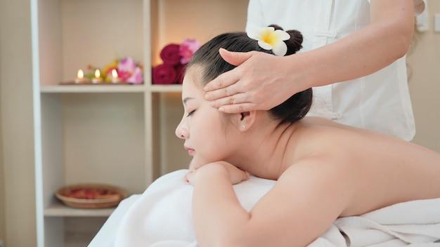 Młoda azjatycka kobieta dostaje zdroju masażu traktowanie przy piękno zdroju salonem. masaż twarzy, masaż relaksacyjny, pielęgnacja skóry i ciała w spa