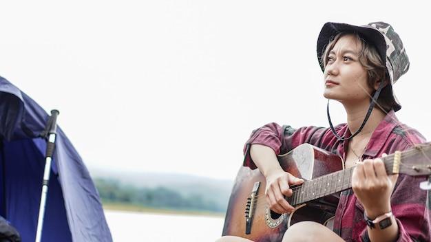 Młoda azjatycka kobieta gra na gitarze na kempingu