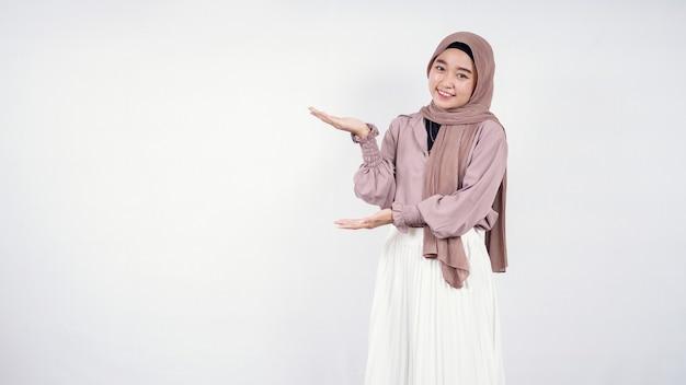 Młoda azjatycka kobieta hidżab wskazująca na puste po prawej stronie na białym tle