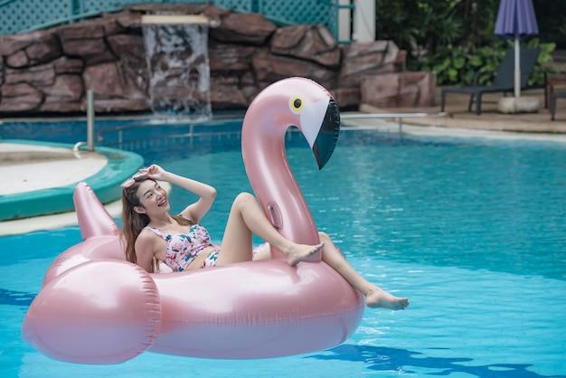 Młoda azjatycka kobieta jedzie na gigantycznym nadmuchiwanym flamingu w pływackim basenie.