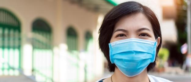 Młoda azjatycka kobieta jest ubranym błękitny twarzy maski pozować