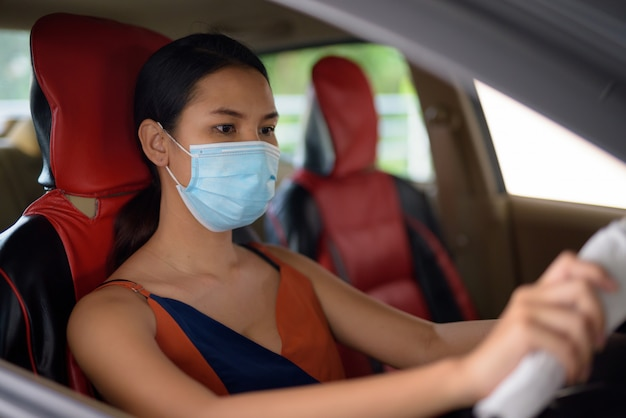 Młoda azjatycka kobieta jest ubranym maskę dla ochrony przed wybuchem wirusa korony słonecznej podczas prowadzenia samochodu