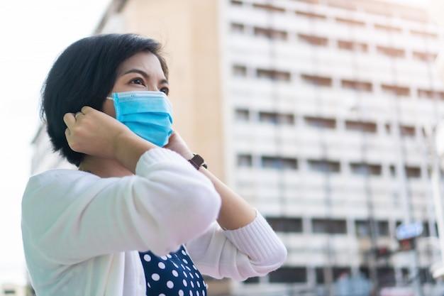 Młoda azjatycka kobieta jest ubranym twarzy maskę przy plenerowym w nowym normalnym życiu