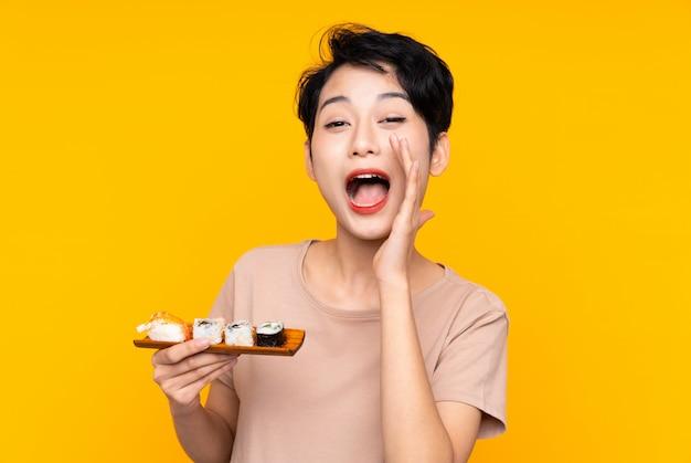 Młoda azjatycka kobieta krzyczy z usta szeroko otwarty z suszi