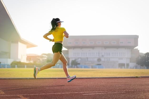 Młoda azjatycka kobieta lekkoatletka biegacza jogging na bieżni na stadionie miejskim w słoneczny poranek, aby zachować kondycję i zdrowy styl życia. młoda kobieta fitness działa na torze stadionu. sport i rekreacja