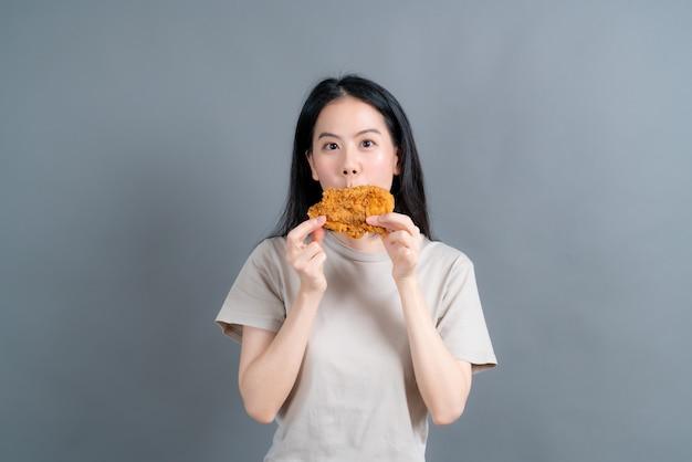 Młoda azjatycka kobieta ma na sobie koszulkę ze szczęśliwą twarzą i cieszy się jedzeniem smażonego kurczaka na szarym tle