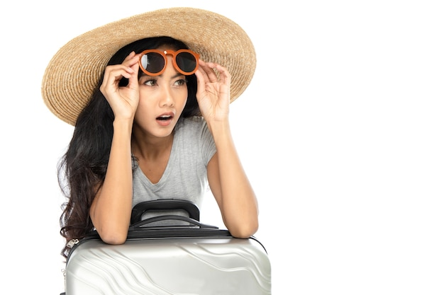 Młoda azjatycka kobieta ma na sobie słomkowy kapelusz z szerokim rondem i okulary przeciwsłoneczne